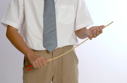 Posed pix of teacher with cane and ruler